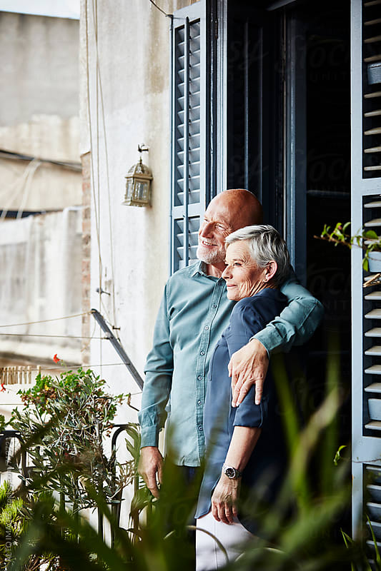 Senior Couple Embracing On Balcony by ALTO IMAGES for Stocksy United