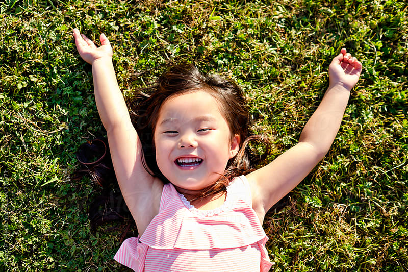 Happy Asian girl outdoor in a park by Suprijono Suharjoto for Stocksy United
