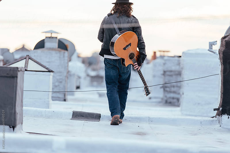 Young musician has guitar on rooftop  by HOWL for Stocksy United