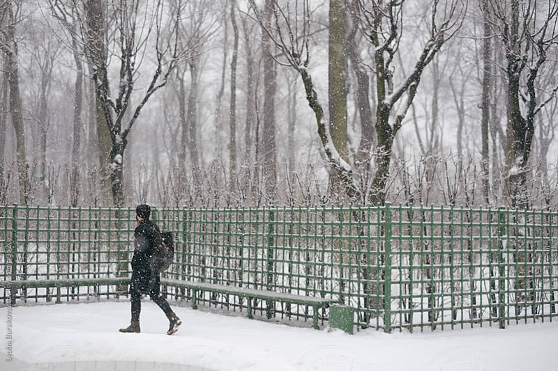 Man walking in park in snow by Lyuba Burakova for Stocksy United