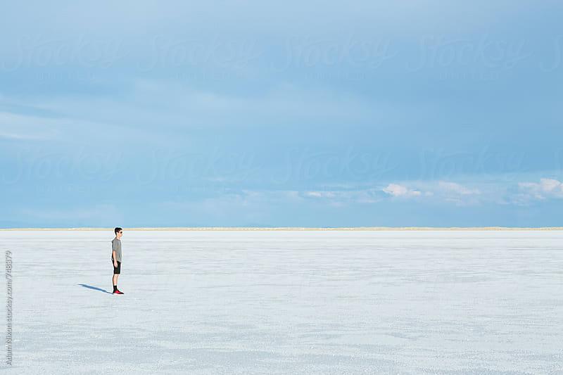 Teenage boy standing on the vast salt flats of Utah by Adam Nixon for Stocksy United
