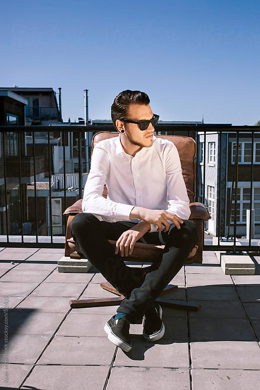 Hip young man with sunglasses sitting in a chair. by Koen Meershoek for Stocksy United