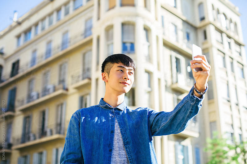 Stylish young asian man taking photos with mobile phone in the street. by BONNINSTUDIO for Stocksy United