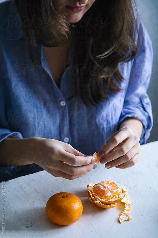 Woman peeling tangerines by Danil Nevsky for Stocksy United