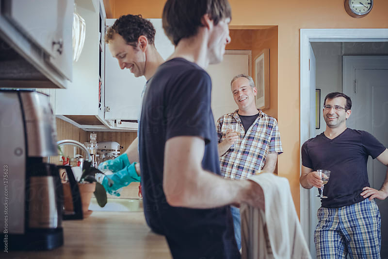 Gay Couple Doing Domestic Chore of Washing Dishes in Kitchen at Home after Dinner with Guests by Joselito Briones for Stocksy United