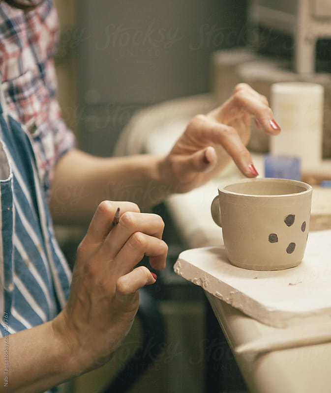 A woman working on handmade ceramic cup by Nabi Tang for Stocksy United