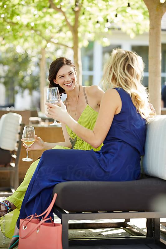 Woman Holding Wineglass While Looking At Friend At Outdoor Restaurant by Trinette Reed for Stocksy United