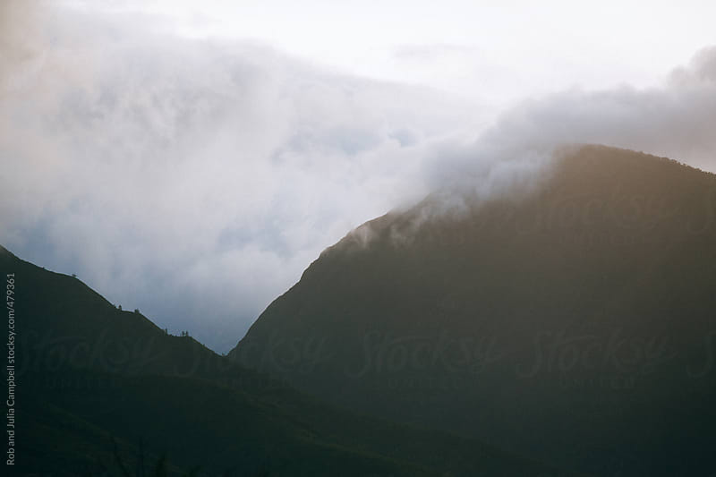 Rain clouds gathering over tropical mountains or hills by Rob and Julia Campbell for Stocksy United