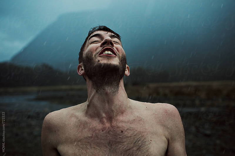 Youthful man howls into the air during a summer rainstorm by HOWL for Stocksy United