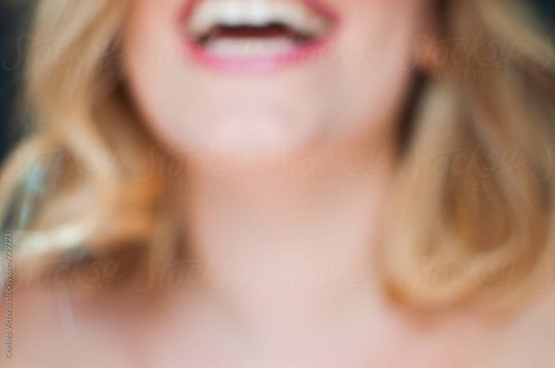 An out of focus woman laughing by Chelsea Victoria for Stocksy United