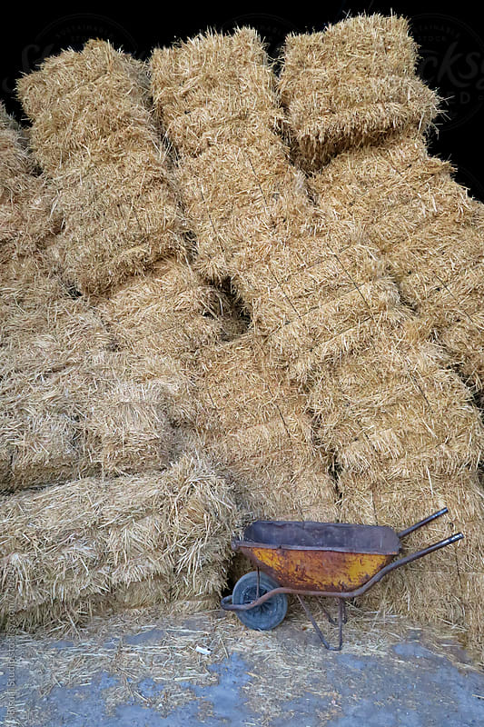 Bales of hay and a wheelbarrow by Bisual Studio for Stocksy United