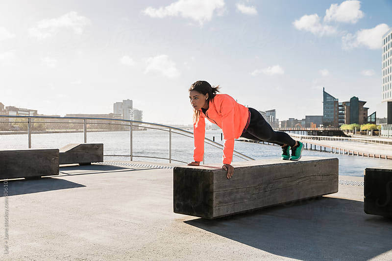 Female mixed race athlete doing pushups on a bench by Lior + Lone for Stocksy United