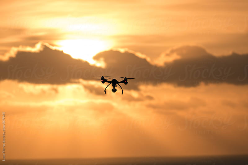Drone flying in the cloudy sunset by Luca Pierro for Stocksy United