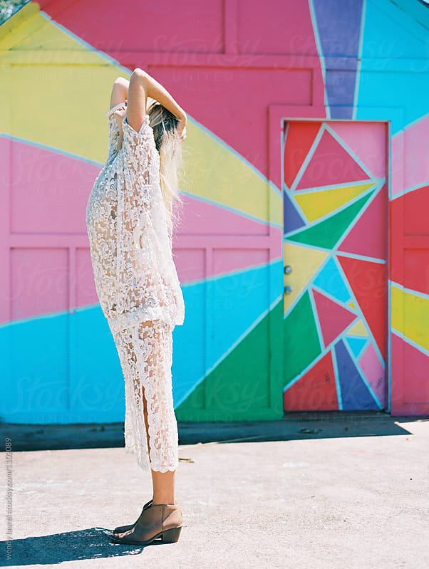 girl in lace dress against colored wall by wendy laurel for Stocksy United