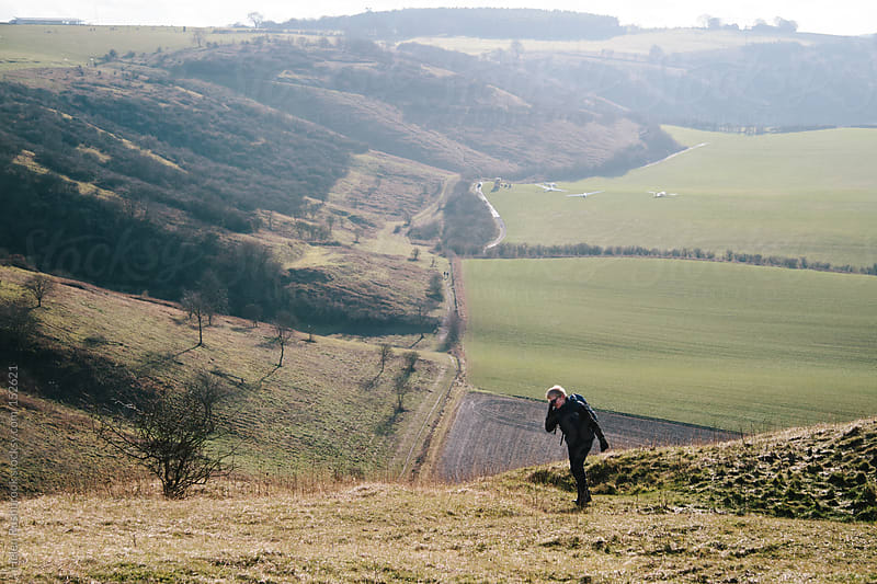 Teenage boy walking up a hill by Helen Rushbrook for Stocksy United