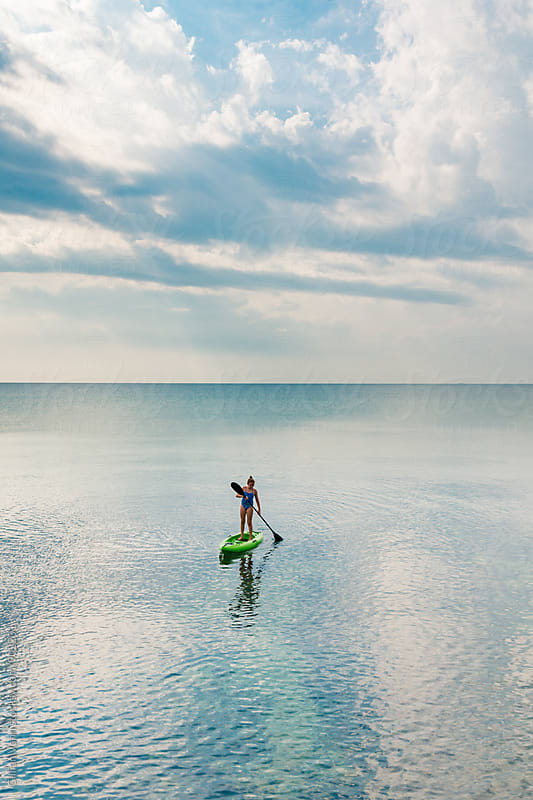 teen girl standing on kayak in the ocean by Gillian Vann for Stocksy United
