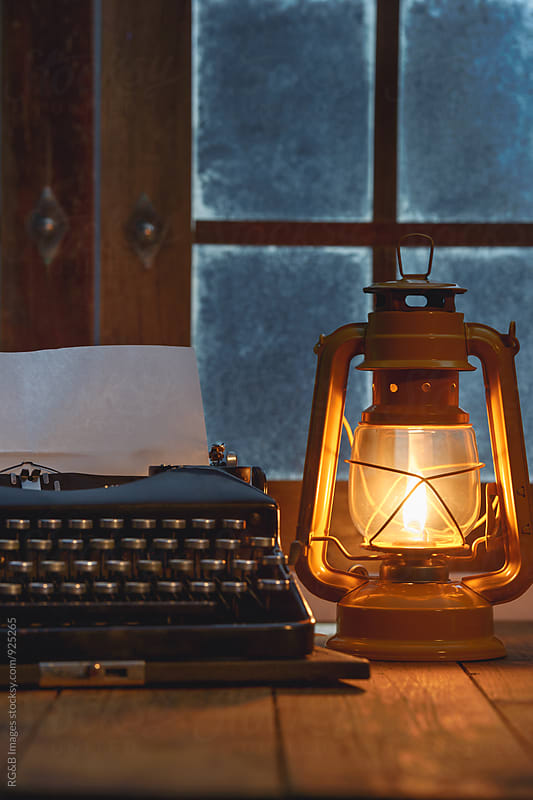 Vintage typewriter under oil lamp light by RG&B Images for Stocksy United