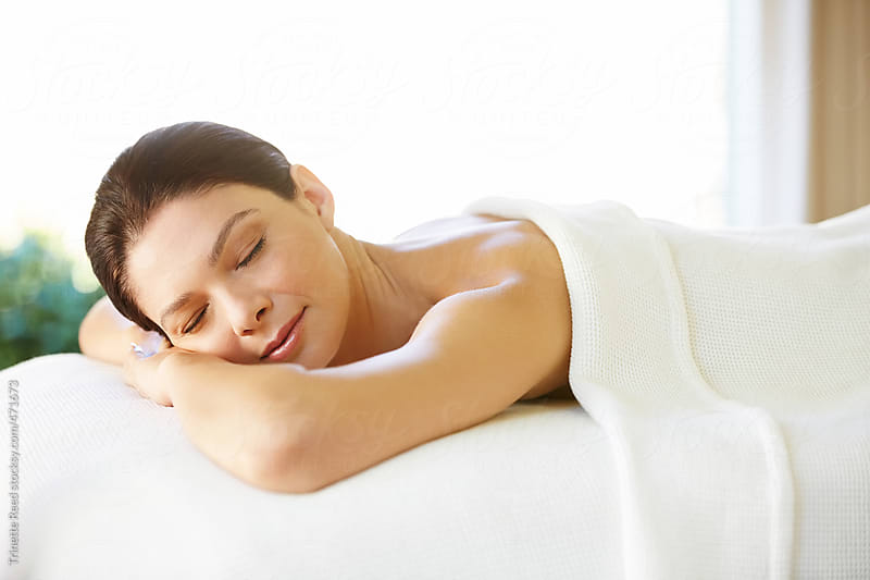 Beautiful Woman With Eyes Closed Lying On Massage Table by Trinette Reed for Stocksy United