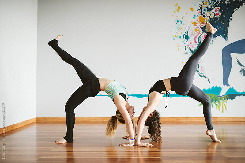 Two women doing backbends in yoga class. by Kate Daigneault for Stocksy United