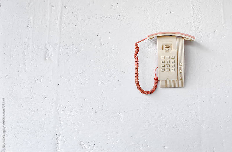 Dead telephone hanging on white wall by Saptak Ganguly for Stocksy United