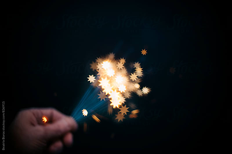 Intentionally blurred hand golding blurry sparklers creating star shapes by Beatrix Boros for Stocksy United