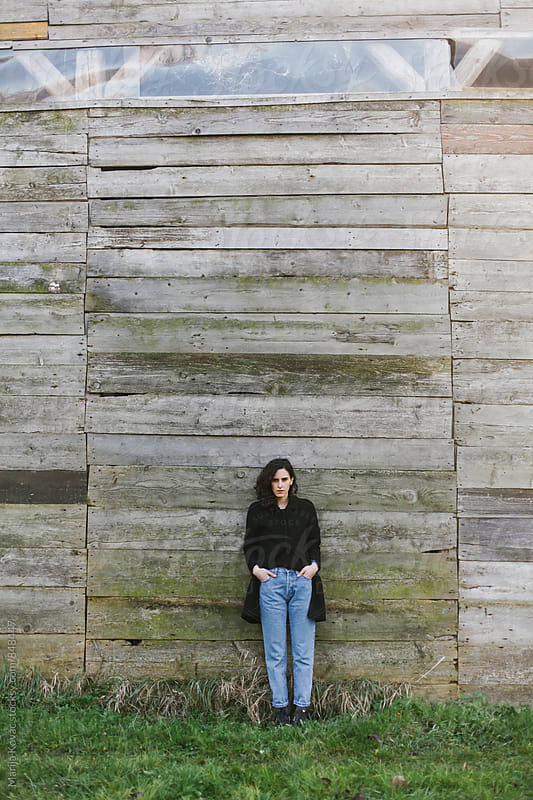 Woman in front of a wooden wall, vertical by Marija Kovac for Stocksy United