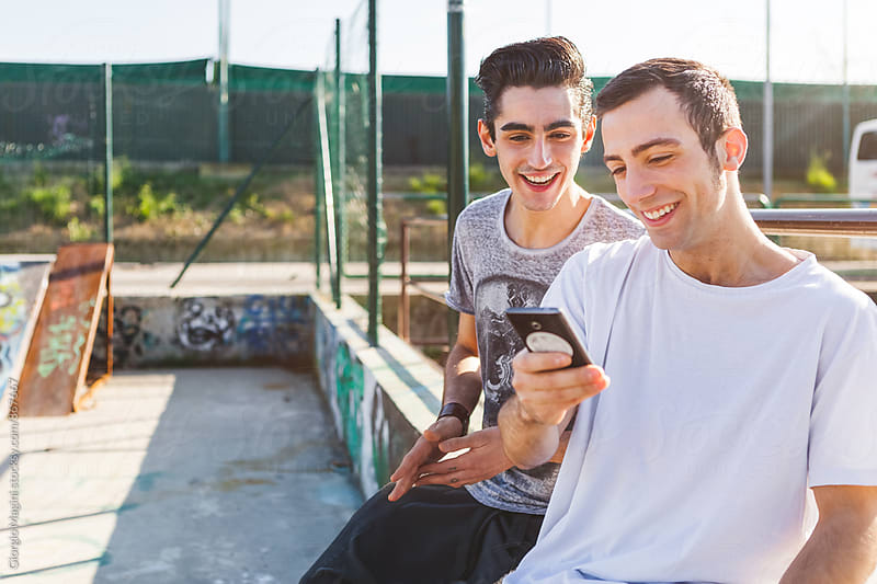 Two Young Friends Having Fun with a Smart Phone at the Skatepark by Giorgio Magini for Stocksy United