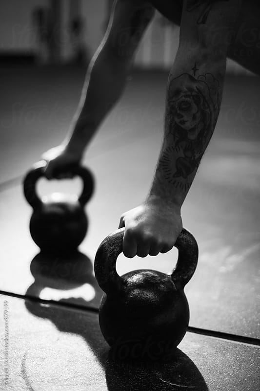 Close up of hands with weight kettles doing push ups by Miquel Llonch for Stocksy United