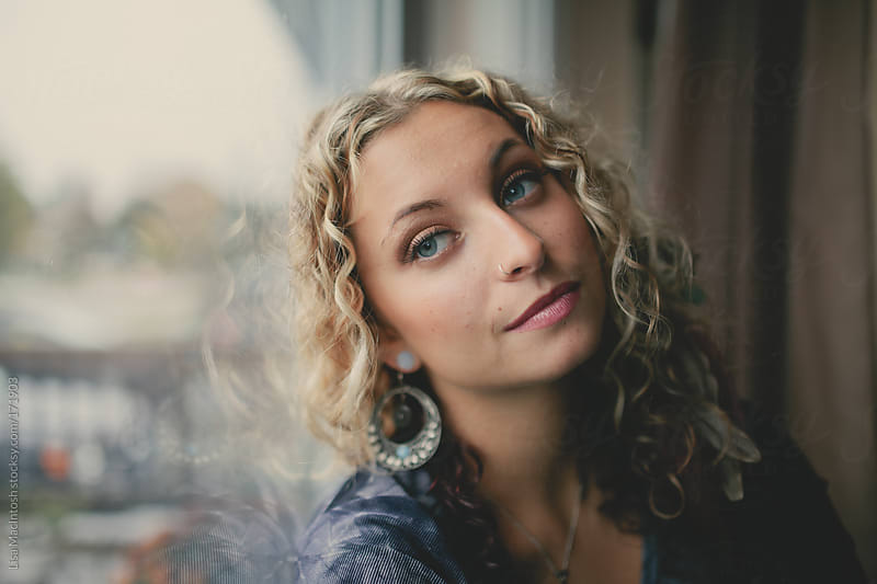 beautiful blonde-curly haired girl with silver earrings leaning against window by Lisa MacIntosh for Stocksy United