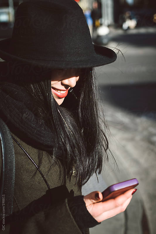 Young smiling woman using a phone in the street by GIC for Stocksy United
