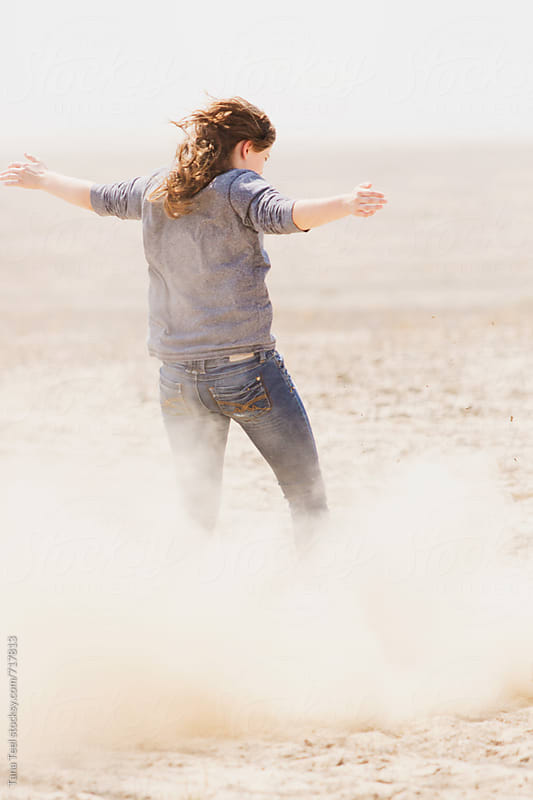 young woman holds arms out while dust blows around her by Tana Teel for Stocksy United
