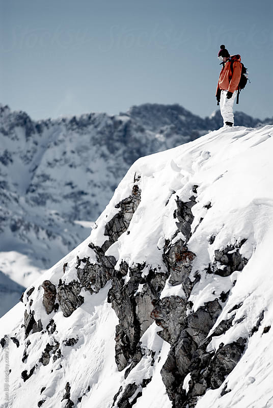 snowboarder checking cliff drop in the snow by Jan Bijl for Stocksy United