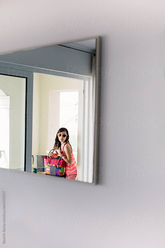 Girl's reflection in the mirror, while she is on the balcony with her bag by Beatrix Boros for Stocksy United