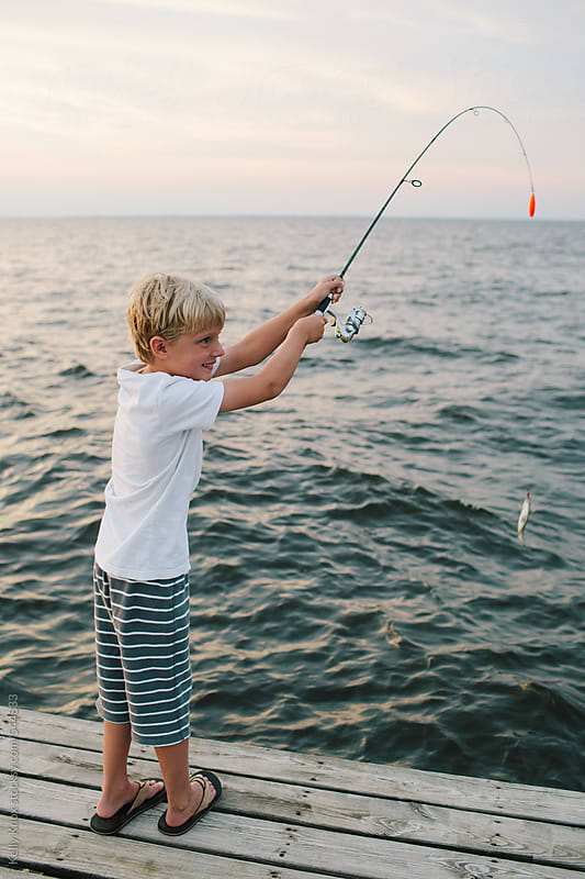 boy reels in a fish he has caught with a fishing pole by Kelly Knox for Stocksy United