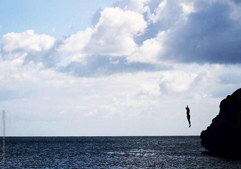 A silhouetted male jumping into the sea. by Helen Rushbrook for Stocksy United