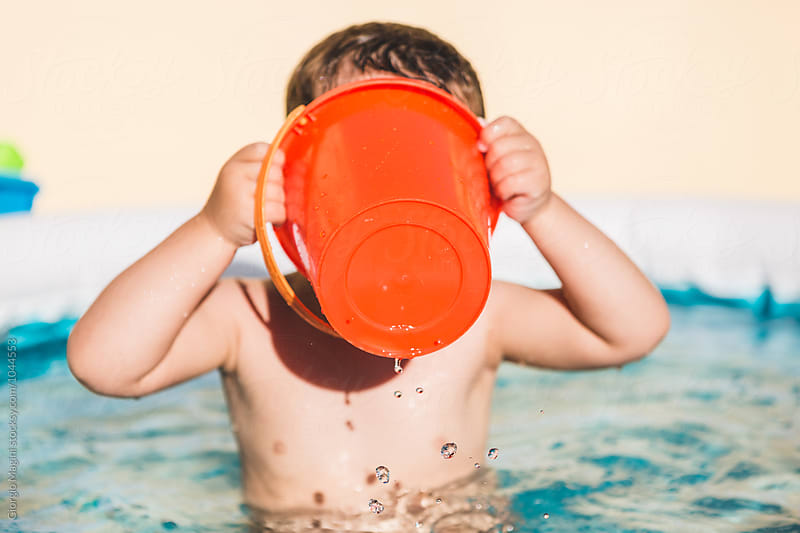 Toddler Playing with a Bucket in a Small Wading Pool Outdoors by Giorgio Magini for Stocksy United