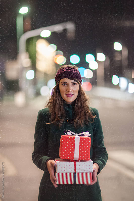 Woman Standing on the Street with Pile of Gifts by Mosuno for Stocksy United