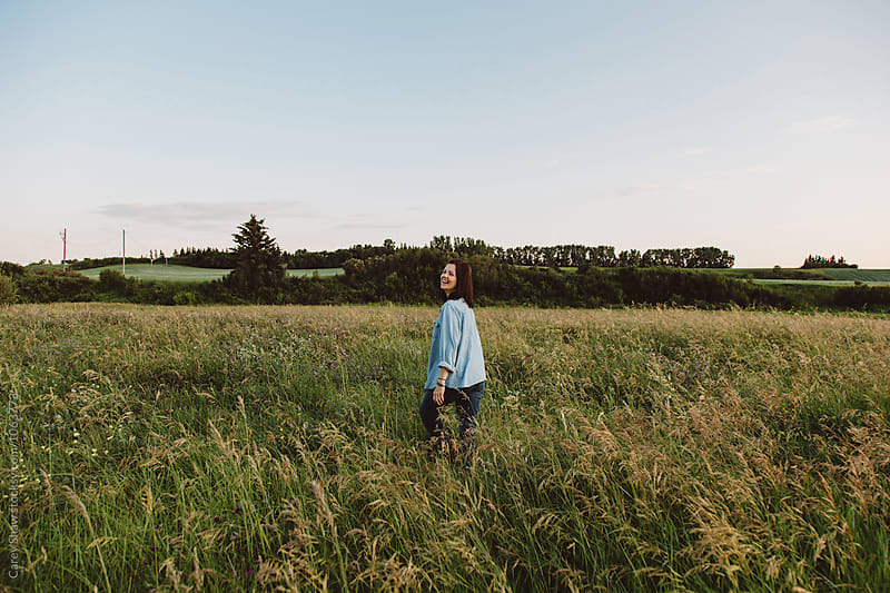 Woman walking through field of grass by Carey Shaw for Stocksy United