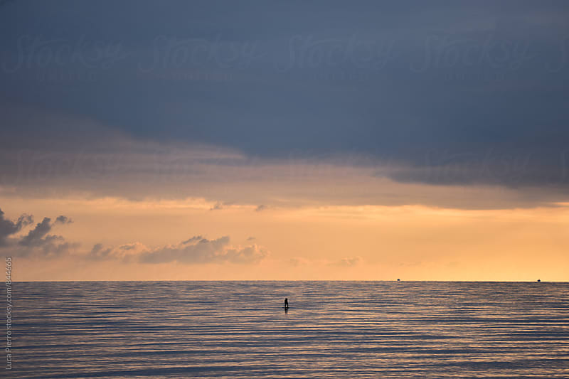 Silhouette Of Man Paddleboarding At Sunset by Luca Pierro for Stocksy United