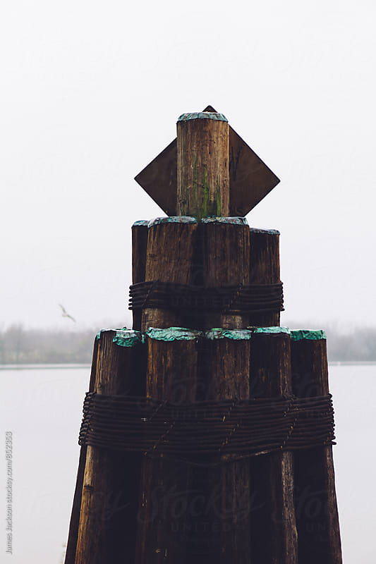 Fender pile at docks on a foggy river. by James Jackson for Stocksy United