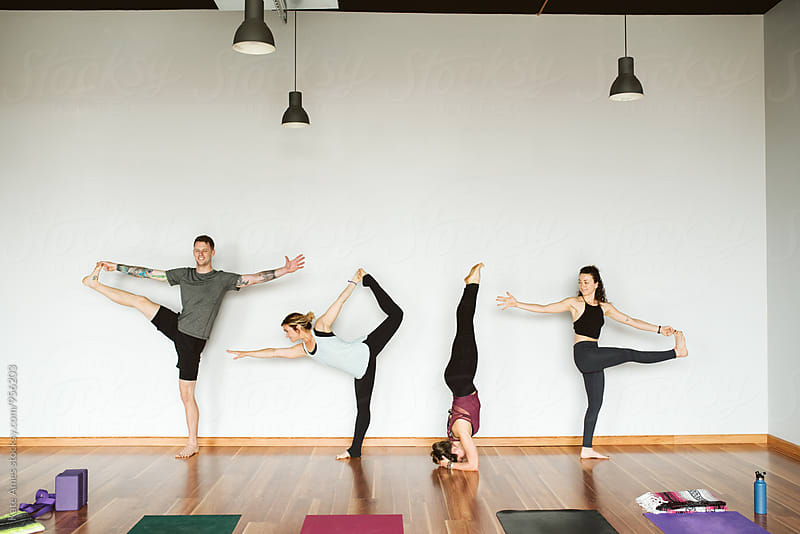Group of young friends doing various yoga poses by Kate Daigneault for Stocksy United