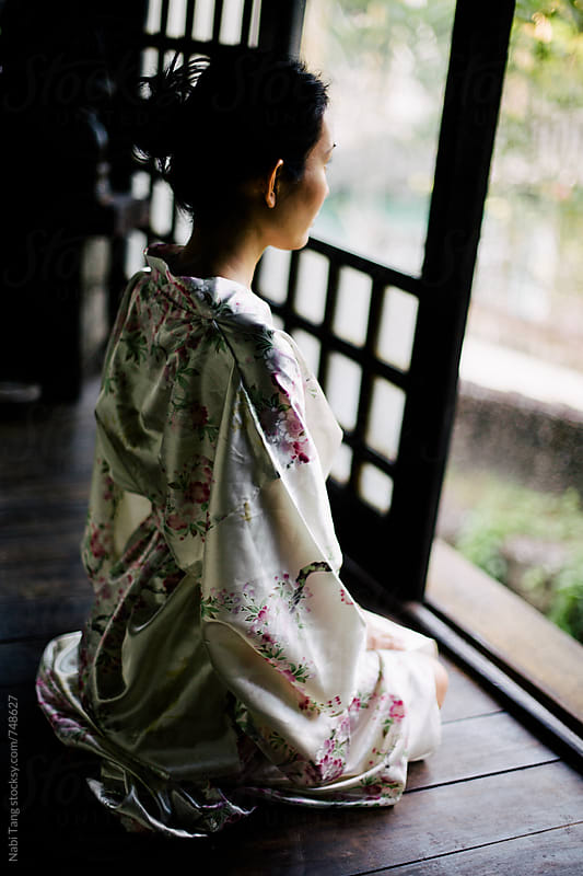 Beautiful Japanese woman looking outside to the garden by Nabi Tang for Stocksy United