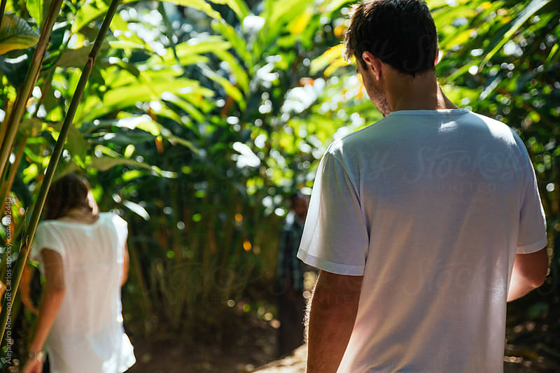 Two young travelers trekking down a hill crossing through tropical countryside by Alejandro Moreno de Carlos for Stocksy United