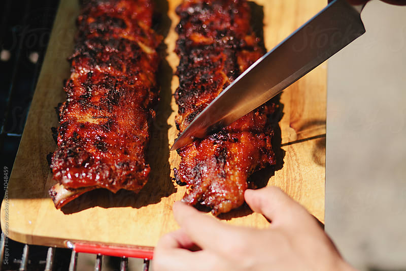 man cuts of pork ribs in barbecue sauce by Sergey Filimonov for Stocksy United