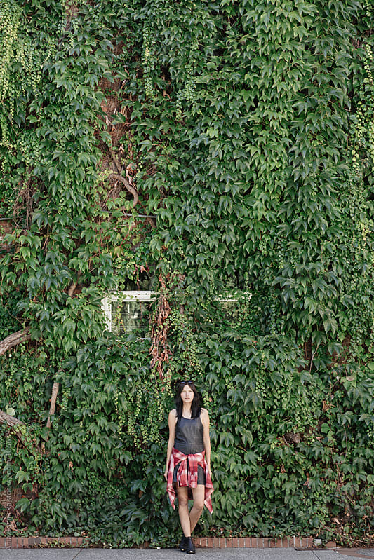 A woman standing against a green vine wall by Ania Boniecka for Stocksy United