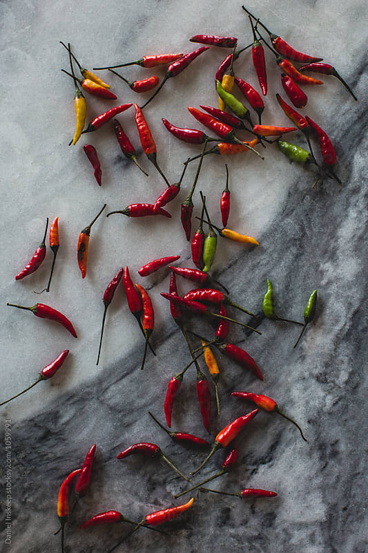Thai Bird's Eye Chilis on a Marble Slab by Daniel Inskeep for Stocksy United