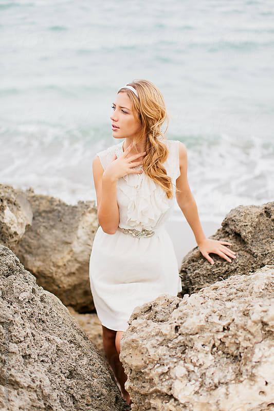 Girl in a white dress on a rocky beach by Ellie Baygulov for Stocksy United