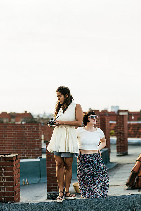 Female couple on a rooftop taking photographs by VegterFoto for Stocksy United