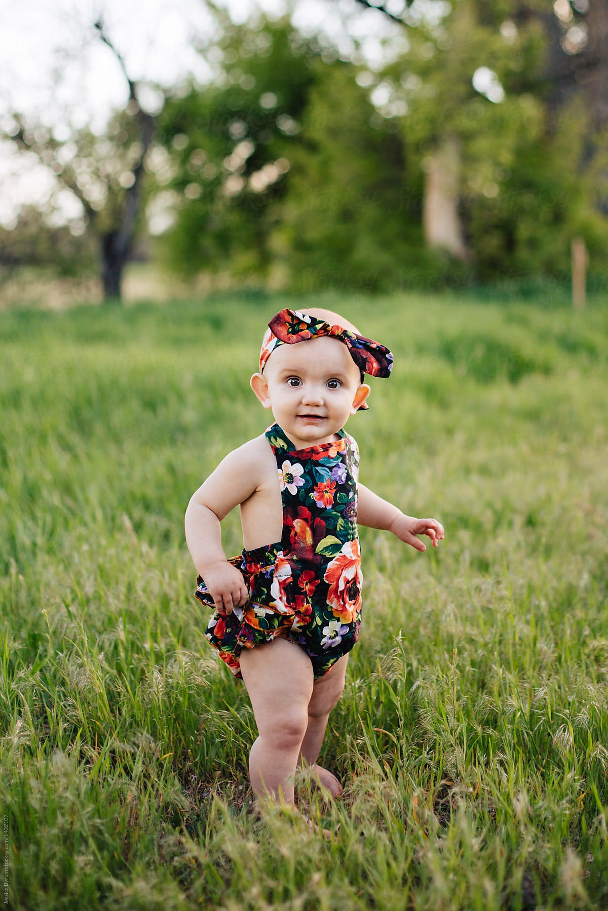 Cute one-year old girl in floral romper and headband outside in tall grass.