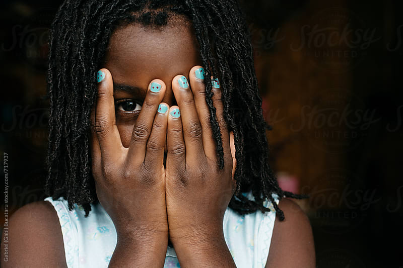 African American girl peeking behind her hands by Gabriel (Gabi) Bucataru for Stocksy United